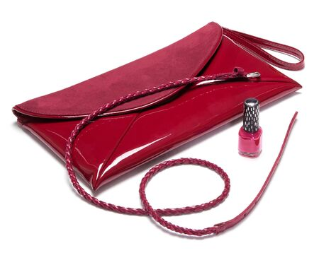 suede belt: Patent leather and suede envelope clutch bag, skinny braided belt and nail polish burgundy color on white background Stock Photo
