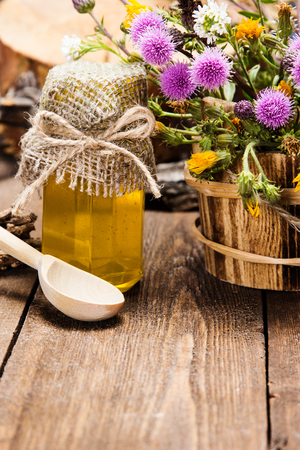 ligneous: Bottle filled with fresh, raw honey, wooden spoon, bouquet of wildflowers in ligneous basket on wooden planks