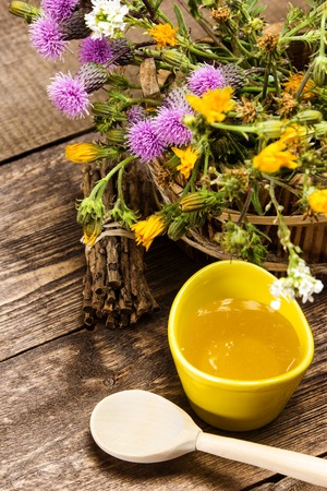 ligneous: Ceramic cup filled with fresh, raw honey, wooden spoon, bouquet of wildflowers in ligneous basket on wooden planks