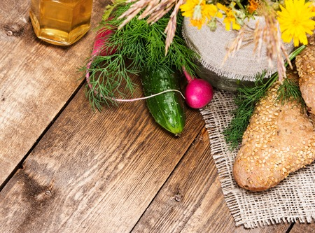 Organic farming food. Freshly baked grain bread with sesame, cucumber, radish, dill, vegetable oil on burlap napkin with bouquet of wild flowers. Wooden planks background. Copy space