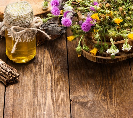 Bottle filled with fresh, raw honey and bouquet of wildflowers in ligneous basket on wooden planks
