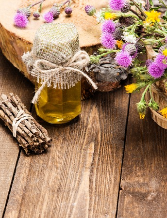 ligneous: Bottle filled with fresh, raw honey and bouquet of wildflowers in ligneous basket on wooden planks