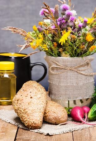comiendo pan: comida sana sencilla. Reci�n horneado pan integral con s�samo, verduras, aceite de semilla de arpillera en la servilleta con el ramo de flores silvestres. superficie tablones de madera Foto de archivo