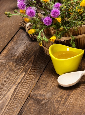 beneficial insect: Ceramic cup filled with fresh, raw honey, wooden spoon, bouquet of wildflowers in ligneous basket on wooden planks. Copy space