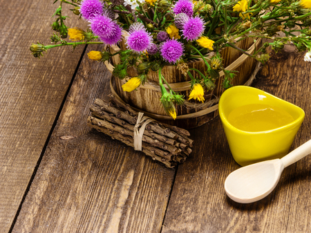 ligneous: Ceramic cup filled with fresh, raw honey, wooden spoon, bouquet of wildflowers in ligneous basket on wooden planks. Copy space