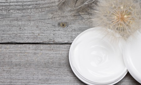 cosmetic product: Concept of light like a dandelion skin care cream. Open jar filled with cream and big fluffy dandelion on old wooden planks. Fresh light texture of cosmetic product for gentle skincare. Copy space