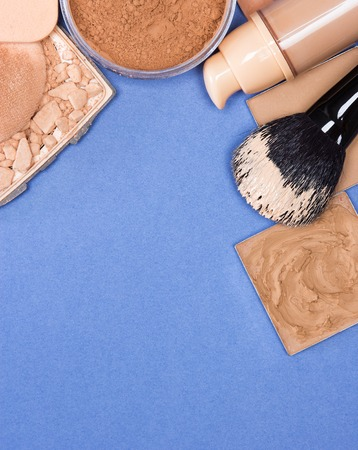 flaws: Close-up of concealer, corrector, open cream foundation bottle and jar filled with loose powder, crushed compact powder, makeup brush and cosmetic sponge on blue surface. Copy space