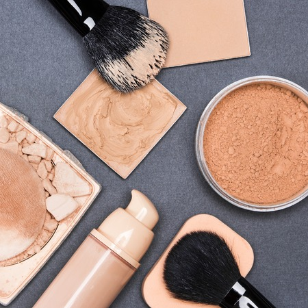 Close-up of concealer, corrector, open cream foundation bottle and jar filled with loose powder, crushed compact powder, makeup brushes and cosmetic sponge on dark gray textured surface