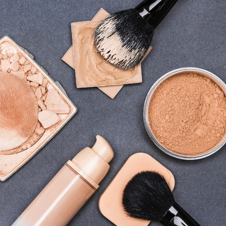 loose skin: Set of makeup products to even out skin tone and complexion: concealer, corrector, open cream foundation bottle, jar of loose powder, crushed compact powder with makeup brushes and cosmetic sponge Stock Photo