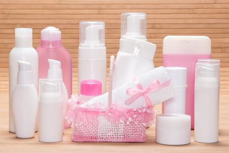 cremas faciales: Diferentes productos cosméticos para el cuidado de la piel en la superficie de madera. Diversos limpiadores faciales, removedores de maquillaje, de día y de noche cremas, desodorante antitranspirante con linda cesta de mimbre y una toalla