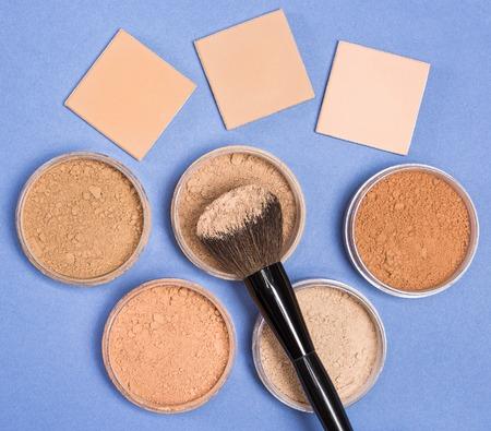 化粧ブラシのクローズ アップは、jar ファイルでいっぱい化粧品ルース パウダーとコンパクトな化粧品粉青の背景にさまざまな色合い。トップ ビュ