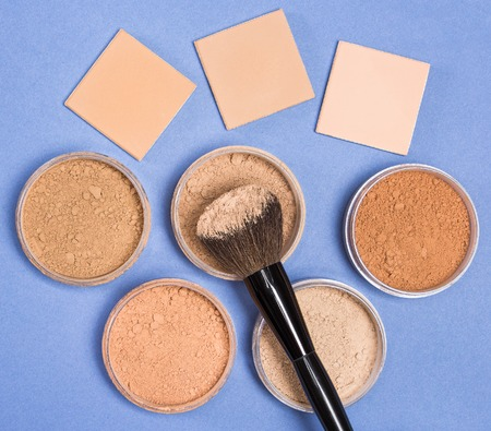 Close-up of makeup brush, jars filled with loose cosmetic powder  and compact cosmetic powder different shades on blue background. Top view Standard-Bild