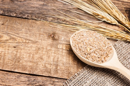oreja: El salvado de trigo en la cuchara de madera con espigas de trigo. Suplemento dietético para mejorar la digestión. Fuente de fibra dietética. Tablones de madera de fondo. Copia espacio