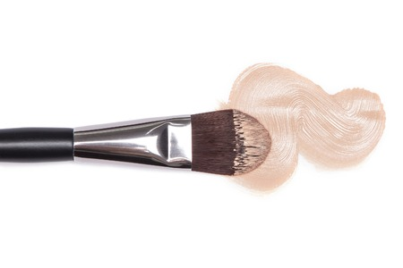 Close-up of makeup brush with smeared liquid foundation on white background. Top view