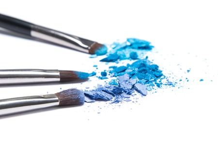 saturated color: Crumbled compact blue eyeshadow different shades with makeup brushes on white background. Side view, very shallow depth of field