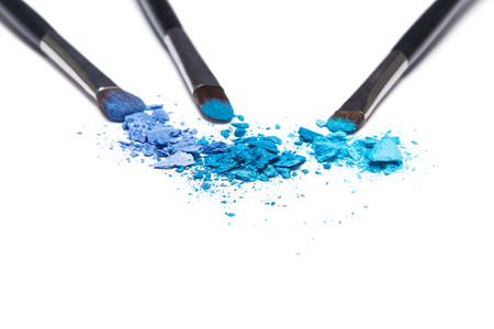 crumbled: Crumbled compact blue eyeshadow different shades with makeup brushes on white background. Shallow depth of field