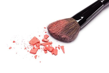 cheekbones: Closeup of crushed powder blush orange color with makeup brush on white background