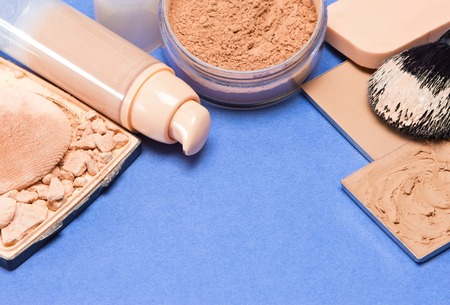 Set of makeup products to make even skin tone: concealer, corrector, cream foundation, loose and crushed compact powder with makeup brush and cosmetic sponge on blue surface. Copy space Фото со стока