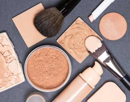 Close-up of concealer pencil, corrector, open liquid foundation bottle and jar of loose powder, crushed compact powder, makeup brushes and cosmetic sponges on gray textured surface Archivio Fotografico