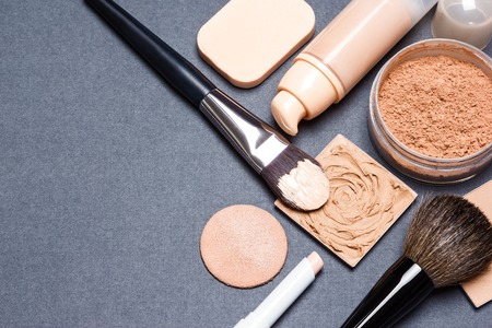 Close-up of corrector, open liquid foundation bottle, jar of loose powder, compact powder, concealer pencil, makeup brushes and cosmetic sponges on gray textured surface. Copy space