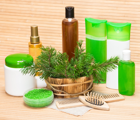 Organic and natural cosmetic products and accessories for hair care: wooden basket filled with pine branches, sea salt, shampoo, conditioner, balm, mask, oil, wooden combs Stock Photo