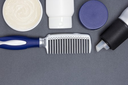 Open jar filled with hair wax and other hair styling products with a comb on gray textured surface. Copy space