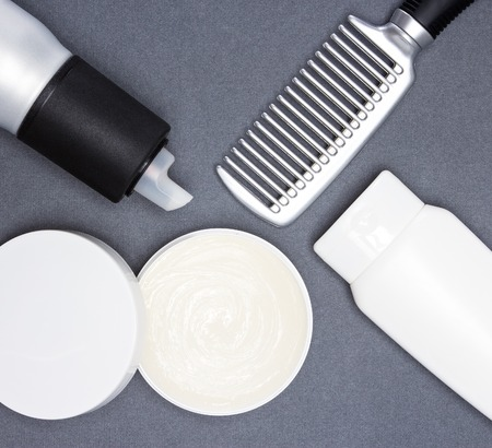 white color: Various hair styling products with a comb on gray textured surface. Color photo in black, white, silver tones Stock Photo