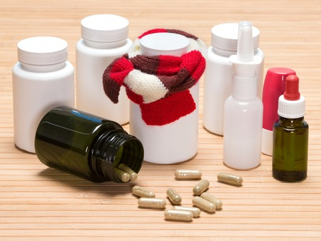 nasal drops: Treatment of colds and flu concept. Jar of pills, tied with knitted scarf, surrounded by jars of medicines, scattered capsules, inhaler, nasal spray and drops with pipette
