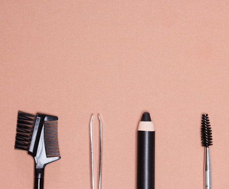 Accessories for care of brows: eyebrow pencil, tweezers, brush and comb on peach colored textured surface. Eyebrow grooming tools. Copy space in the upper portion of the image