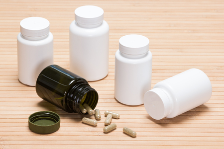 overturned: Overturned open dark green jar with scattered capsules surrounded by white plastic jars of medicines