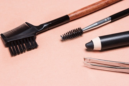 Accessories for care of brows: eyebrow pencil, tweezers, brush and comb on peach colored textured surface. Eyebrow grooming tools