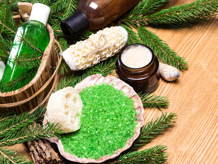 pampering: Spa and pampering products and accessories: sea salt in shell, loofah, wisp of bast, skin care cream, shampoo and shower gel with pumice in wooden basket surrounded by fir branches