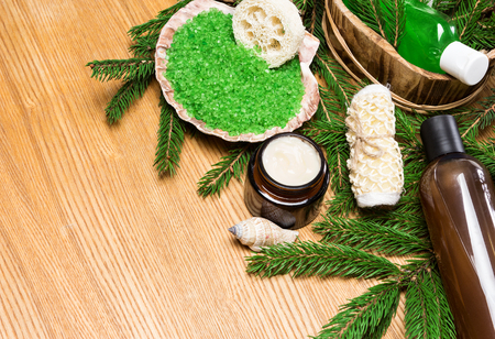 pampering: Spa and pampering products and accessories: sea salt in shell, loofah, wisp of bast, skin care cream, shampoo and shower gel in wooden basket surrounded by fir branches. Copy space Stock Photo