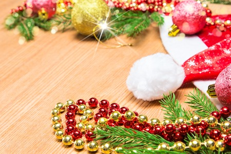 lambent: Christmas and New Year festive background. Christmas balls, beads and hat with spruce branches on wooden surface. Copy space Stock Photo