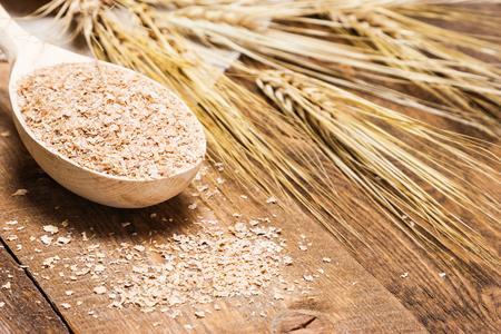 小麦の耳に木のスプーンで小麦ふすまのクローズ アップ。消化を改善するためのサプリメント。食物繊維のソースです。木製の板の背景。浅い被写し界深度