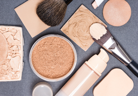 dark skin: Makeup products and accessories to even out skin tone and complexion on gray textured surface