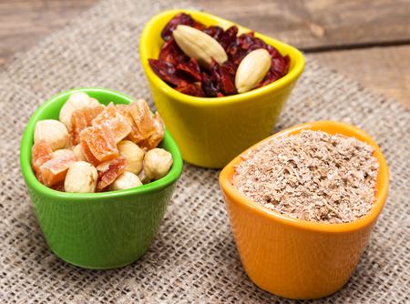 natural health: Natural health products. Ceramic cups filled with wheat bran, mixtures of nuts with dried fruits and berries. Peeled hazelnut, almond, papaya, cranberries. Side view, shallow depth of field