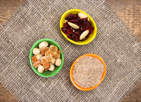 natural health: Natural health products. Ceramic cups filled with wheat bran, mixtures of nuts with dried fruits and berries. Peeled hazelnut, almond, papaya, cranberries. Top view