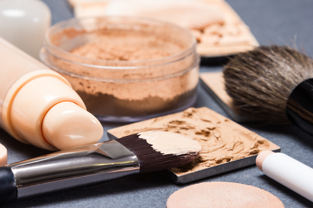 Makeup products and accessories to even out skin tone and complexion on gray textured surface. Side view, very shallow depth of field, focus on bristle of brush with liquid foundation