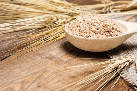 Close-up of wheat bran in wooden spoon with wheat ears. Dietary supplement to improve digestion. Source of dietary fiber. Wooden planks background. Side view, shallow depth of field