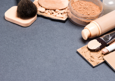 loose skin: Makeup products and accessories to even out skin tone and complexion: correctors, liquid foundation, loose and compact powder, concealer pencil, makeup brushes and cosmetic sponge. Copy space