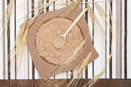 Bamboo plate and wooden spoon filled with wheat bran surrounded by wheat ears on striped cloth napkin and wooden planks. Dietary supplement to improve digestion. Source of dietary fiber