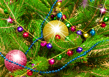 lambent: Close-up of Christmas tree branches decorated with shining Christmas balls, garland of varicolored bells and beads. Bright New Year festive background