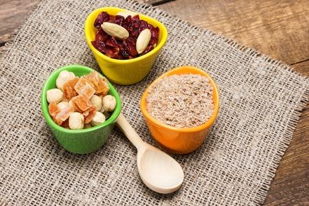 natural health: Natural health products with wooden spoon on burlap napkin. Ceramic cups filled with wheat bran, mixtures of nuts with dried fruits and berries. Peeled hazelnut, almond, papaya, cranberries