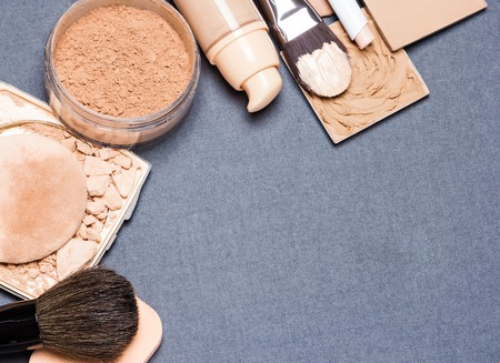 Makeup products and accessories to even out skin tone and complexion: correctors, liquid foundation, loose and compact powder, concealer pencil, makeup brushes and cosmetic sponge. Copy space