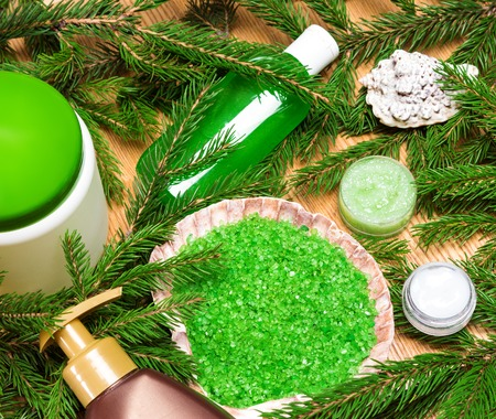 organic spa: Different natural beauty products with branches of conifer tree on wooden surface. Top view. Organic spa cosmetics Stock Photo