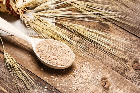 Wheat bran in wooden spoon with wheat ears. Dietary supplement to improve digestion. Source of dietary fiber. Wooden planks background Standard-Bild