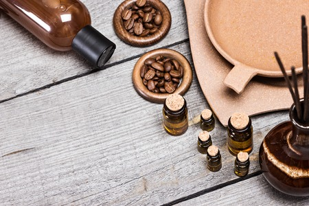 crock: Small glass vials of aromatic essential oils next to crock with incense sticks, bamboo plate with water and coffee beans, massage oil bottle on old wooden planks. Grey and brown colors. Copy space Stock Photo