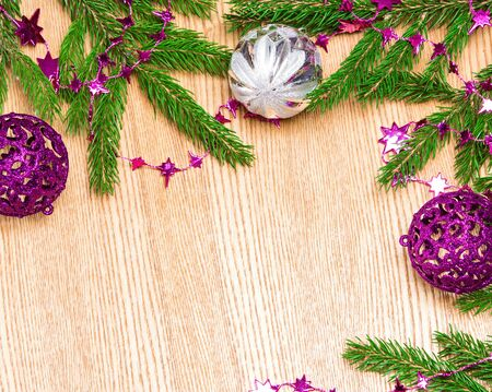 lambent: Christmas and New Year festive background. Fresh green spruce branches with star shaped beads purple color and Christmas balls on wooden surface. Copy space