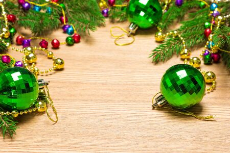 lambent: Christmas and New Year festive background. Green Christmas balls, garland of varicolored bells and beads golden color with spruce branches on wooden surface. Copy space